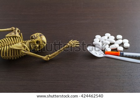Skull and drugs with insulin syringe. Next to them are a spoon with white powder, which is similar to heroin on wooden  background,touch-up in still life concept. - stock photo