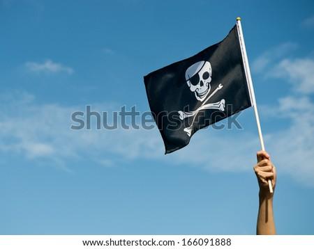 skull flag in hand waving on blue sky background. - stock photo