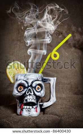 Skull mug with lemon and yellow stick with steam from inside at textured background on Halloween party - stock photo