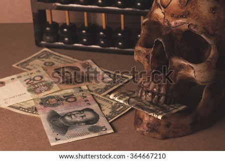 skull on old wood with banknote yuan and dollar in still life style - stock photo