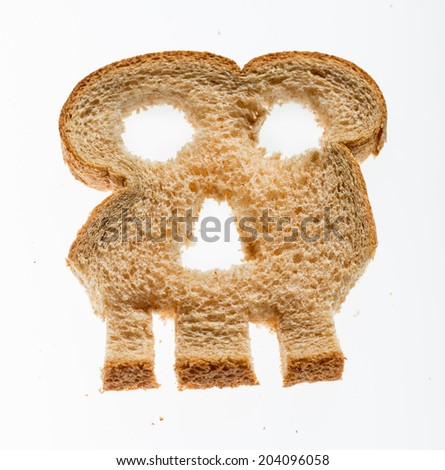 Skull shaped piece of bread cut from whole wheat loaf to illustrate danger from gluten in wheat products - stock photo