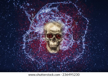 Skull with blue water splashing around it with red glowing lines behind it as well - stock photo