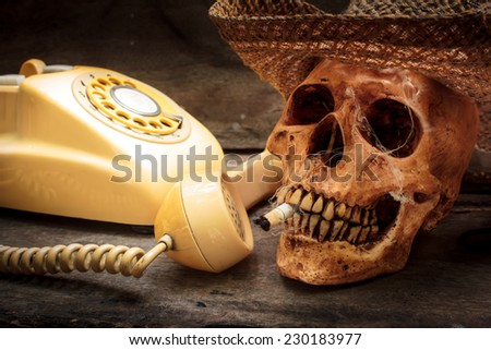 Skull with cigarette, and old wood background.