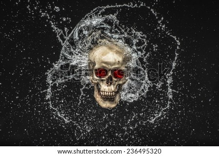 Skull with water splashing around it over a black background - stock photo