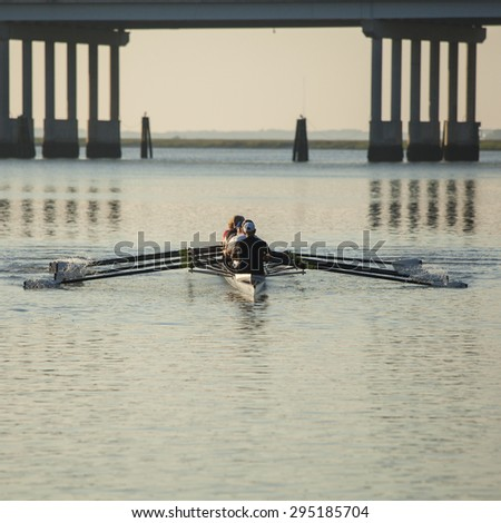 skulls rowing team rowing on open water with bridge in background - stock photo