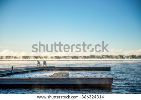 Sky and a dock on Georgian Bay, Muskoka chairs at the end.  - stock photo