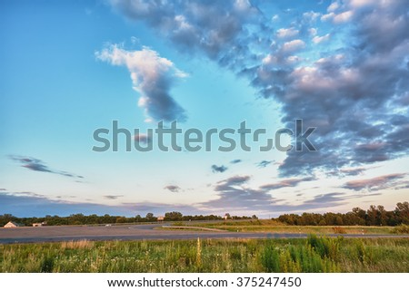 Sky and clouds over the highway and meadows at sunset - stock photo