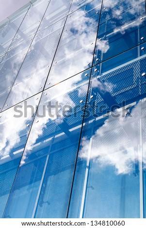 Sky and clouds reflected in a modern building glass facade - stock photo