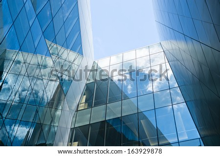 Sky and clouds reflected in windows of modern office building.