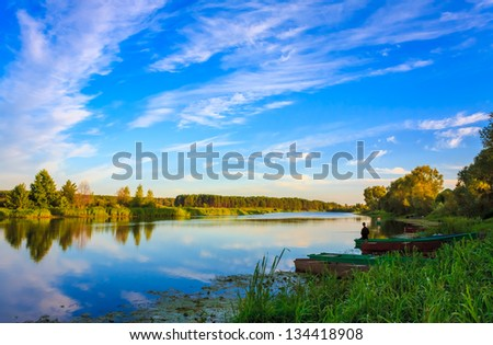Sky And Clouds Reflection On Lake River - stock photo