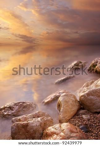Sky and stones during sundown. Bright seascape - stock photo