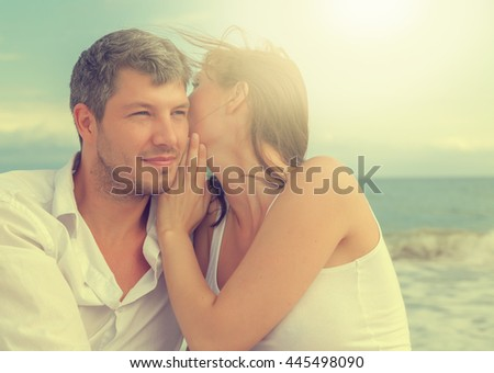 sky and sun behind whispering couple - stock photo