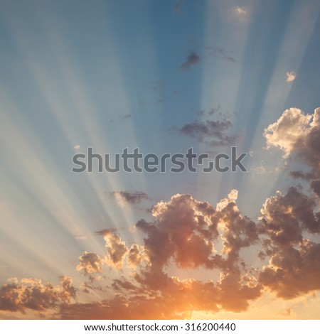 Sky at sunset with rays of the sun through the clouds - stock photo
