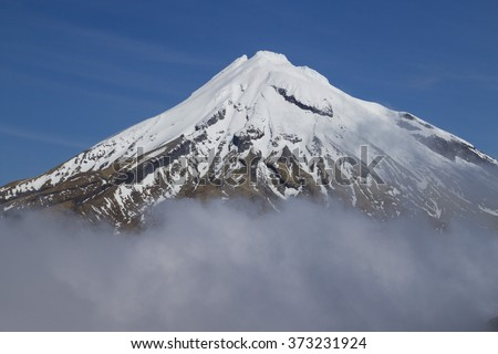 sky - high active dangerous volcano Taranaki or mount egmont in clouds with snow on the top located in beautiful pure wild national park - stock photo