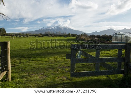 sky - high active dangerous volcano Taranaki or mount egmont in clouds with snow on the top located in beautiful pure wild national park view from garden  - stock photo