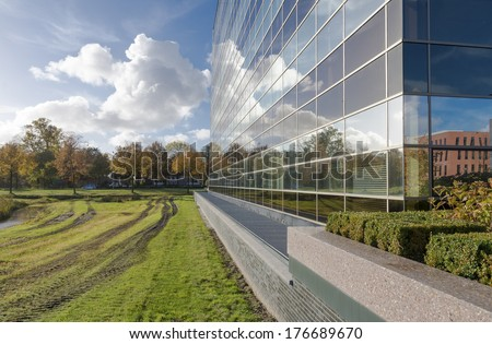 sky reflected in a modern office building glass facade - stock photo