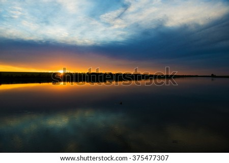 Sky reflecting in the lake as in a mirror. Golden vivid sunset sky background with clouds and brightly sunbeams. Colorful sky panorama with orange sun rays.