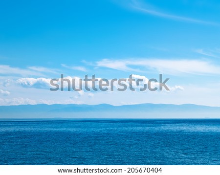 Sky, sea and mountainous island in the haze. Abstract travel background - stock photo