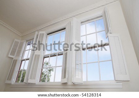 Sky seen through windows with louver shutters - stock photo