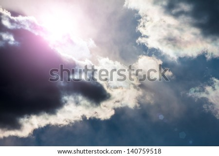 Sky with dark clouds and sun. With lens flare. - stock photo