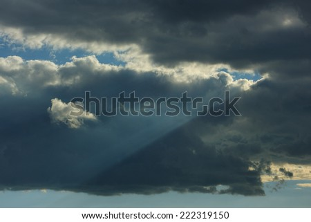 Sky with thunderstorm clouds. Rays of the sun through the storm clouds and a separate small cloud. - stock photo