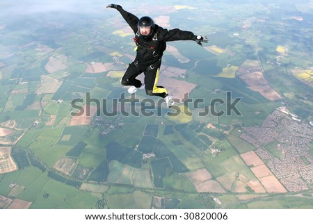Skydiver in a sit position facing the cameraman - stock photo