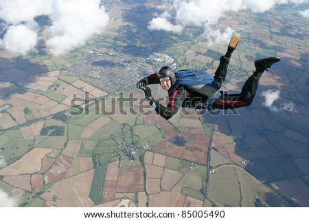 Skydiver in freefall high up in the air on a sunny day - stock photo
