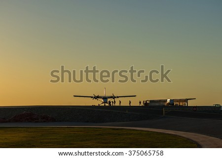 Skydivers are boarding at sunset. - stock photo