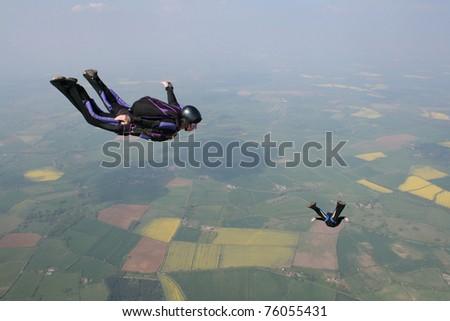 Skydivers flies past cameraman - stock photo