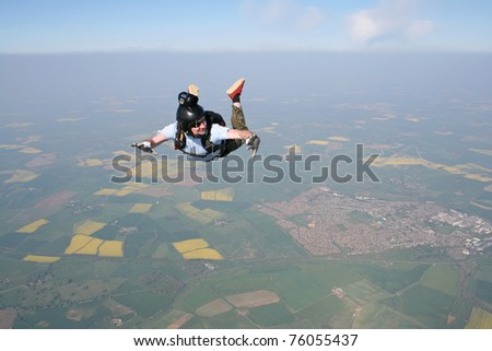 Skydivers looks at his altimeter while in freefall - stock photo