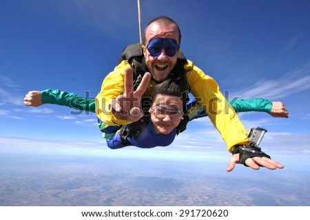 Skydiving. Courageous woman flying through the skies. - stock photo