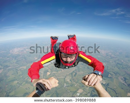 Skydiving senior man holding hands - stock photo