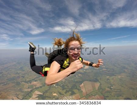 Skydiving smiling beautiful woman - stock photo