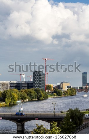 skyline of berlin with canal and dramatic sky. - stock photo