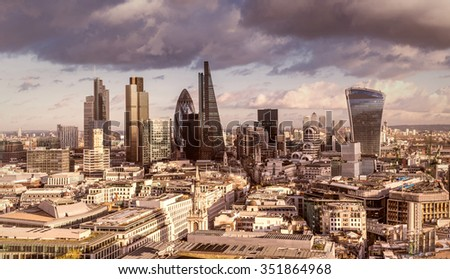 Skyline of Business district of London with dark clouds and Canary Wharf at the background - stock photo