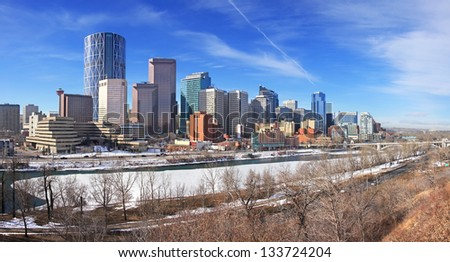 Skyline of Calgary, Alberta, Canada. Bow River partly covered with Snow and Ice. Picture taken March 1, 2013 - stock photo