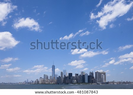 Skyline of downtown Manhattan New York during daytime as seen from a boat. Space for text on sky.