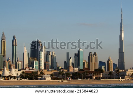 Skyline of Downtown of Dubai (UAE) in the evening. Famous Burj Khalifa, the tallest building in the world. Modern skyscrapers of the city built in the desert. The view from the beach of Persian Gulf.