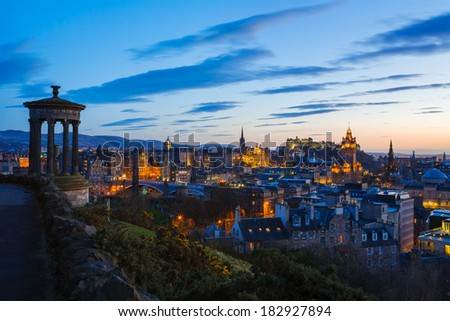 Skyline of Edinburgh at Twilight from Calton Hill, with the silhouette of the Dugald Stewart Monument on the left of frame. - stock photo