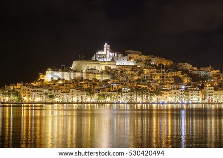 Skyline of Ibiza Dalt Vila downtown at night with light reflections in the water