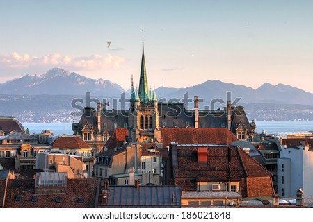 Skyline of Lausanne, Switzerland as seen from the Cathedral hill at sunset zoomed-in on the tower of St-Francois Church. Lake Leman (Lake Geneva) and the French Alps provide a beautiful background. - stock photo