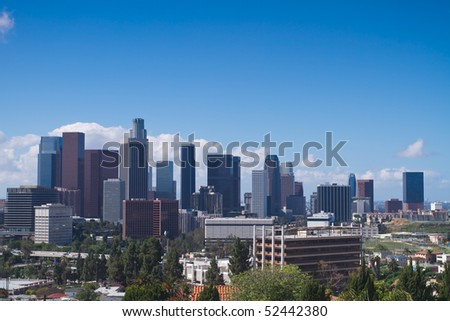 Skyline of Los Angeles shown at early dusk with blue sky.