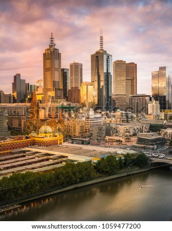 Skyline of Melbourne along the river Yarra from a high vantage point. The sun set is reflecting in the buildings. Flinders Street railyway station can be seen from abov