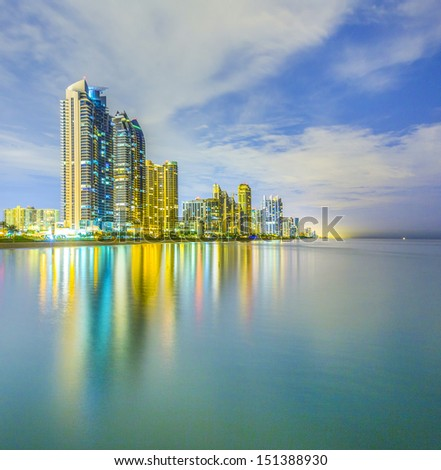 skyline of Miami sunny isles by night with reflections over the ocean - stock photo