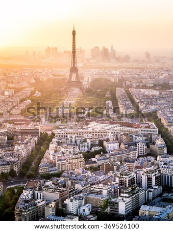 Skyline of Paris, France and Eiffel Tower with houses, streets and parks and with warm, colorful sunset light with business district La Defense in the background - stock photo