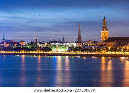 Skyline of Riga seen across the river Daugava after the sunset. The tallest building on the picture is the Riga Dome cathedral, smaller one to the left is St. Saviour's Church  - stock photo
