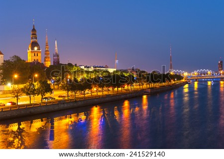 Skyline of Riga seen across the river Daugava after the sunset. Three church towers in the picture are the Riga Dome cathedral,  St. Saviour's Church and St. Peter's church.  - stock photo