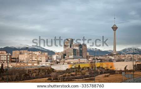 Skyline of Tehran with residential and commercial buildings, Milad Tower and Alborz Mountains. - stock photo