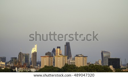 Skyline of the city of London during sunset from Primrose Hill with sun reflections