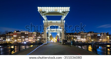Skyline of the Dutch city Amsterdam with a typical bridge and canal and the lights of houses with a blue sky at night - stock photo